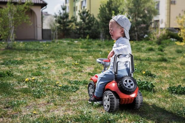 Chłopiec płacze na zabawkarskim samochodzie