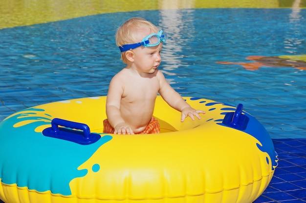 Chłopiec pływać z zabawą w basenie z nadmuchiwaną zabawką w parku wodnym.