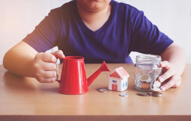 Chłopiec podlewania dom i monety. plan koncepcji domu