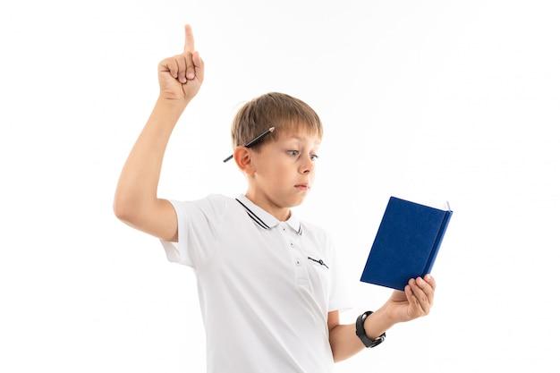 Chłopiec podniósł palec, czytając książkę na białym tle