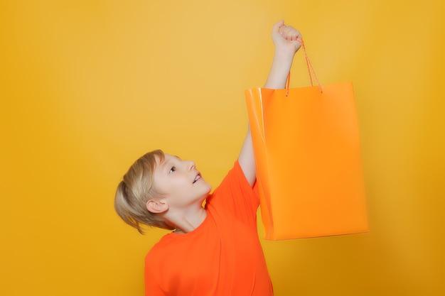 Chłopiec podniósł pomarańczową papierową torbę na zakupy