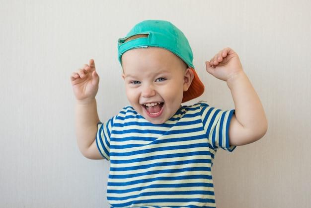 Chłopiec podniósł ręce i się śmieje