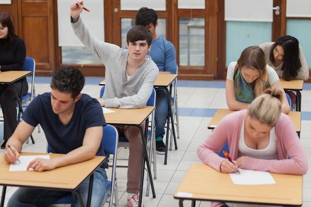 Chłopiec podnosząc rękę podczas egzaminu