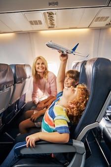 Chłopiec podnoszący nad głową samolot-zabawkę