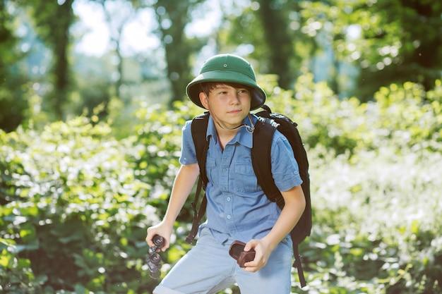 Chłopiec podróżnik w kasku grać w parku.
