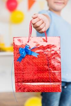 Chłopiec pokazuje czerwoną torbę z błękitnym dekorującym łękiem