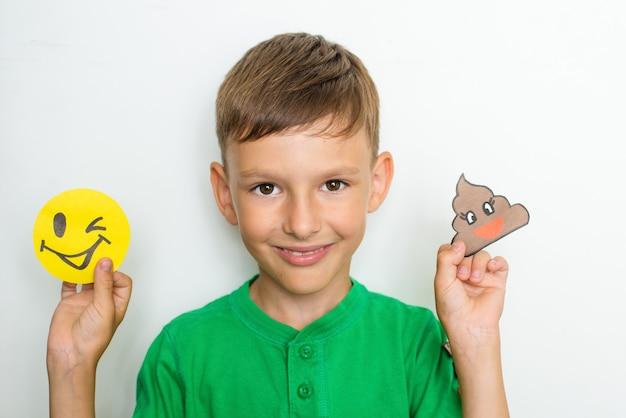 Chłopiec pokazuje emocje i ma zabawne uśmiechy z papieru