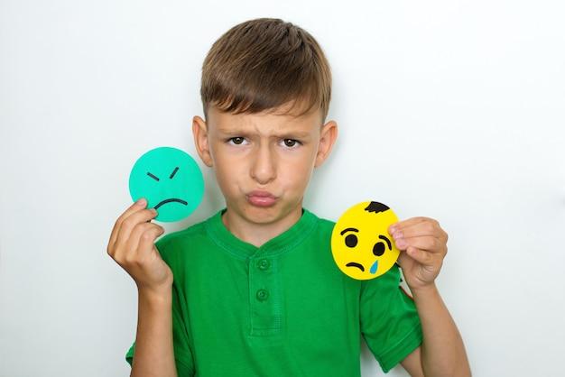 Chłopiec pokazuje emocje i trzyma smutne emotikony z papieru