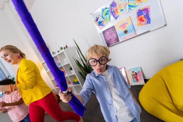 Chłopiec pokazuje język. wesoły uczeń w okularach pokazujący język podczas zabawy po lekcji