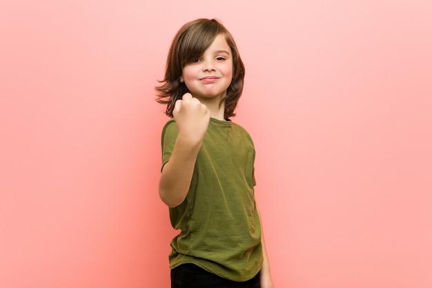 Chłopiec pokazuje pięść kamera, agresywny wyraz twarzy.