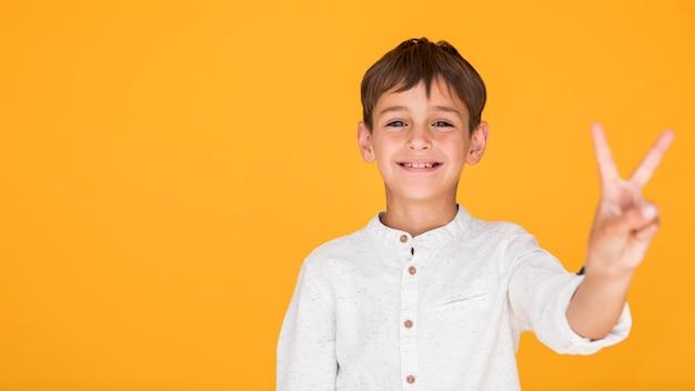 Chłopiec pokazuje znak pokoju z kopii przestrzenią