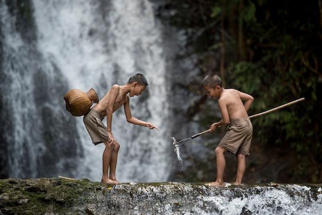 Chłopiec połowów rybackich w rzece. chłopiec połów w rive wsi azja.