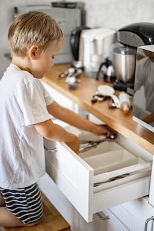 Chłopiec pomaga mamie w kuchni uporządkować rzeczy, układa widelce, łyżki i sztućce