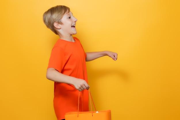 Chłopiec powoli ucieka trzymając w rękach pomarańczową papierową torbę na zakupy