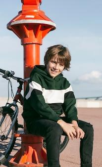 Chłopiec pozuje obok teleskopu na zewnątrz z rowerem