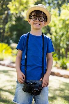 Chłopiec pozuje z kamerą wokoło jego szyi
