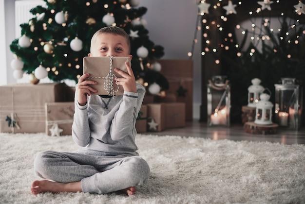 Chłopiec pozuje z prezentem świątecznym