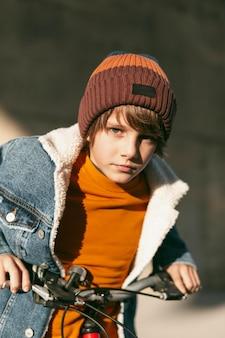 Chłopiec pozuje z rowerem na zewnątrz w mieście