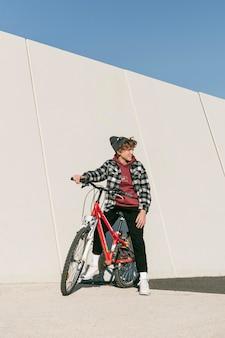 Chłopiec pozuje z rowerem na zewnątrz