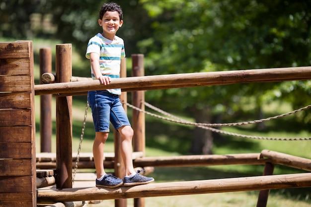 Chłopiec pozycja na boisko przejażdżce w parku