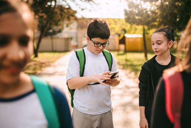Chłopiec pozycja z przyjaciółmi używa mądrze telefon przy boiskiem szkolnym
