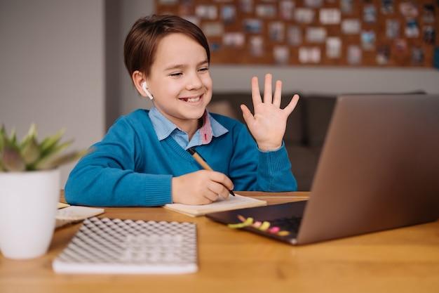 Chłopiec preteen używa laptopa do prowadzenia zajęć online, witając się z nauczycielem
