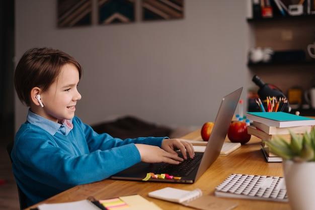 Chłopiec preteen używa laptopa do prowadzenia zajęć online