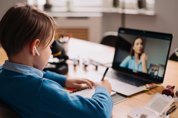 Chłopiec preteen używa laptopa do rozmowy wideo ze swoim nauczycielem