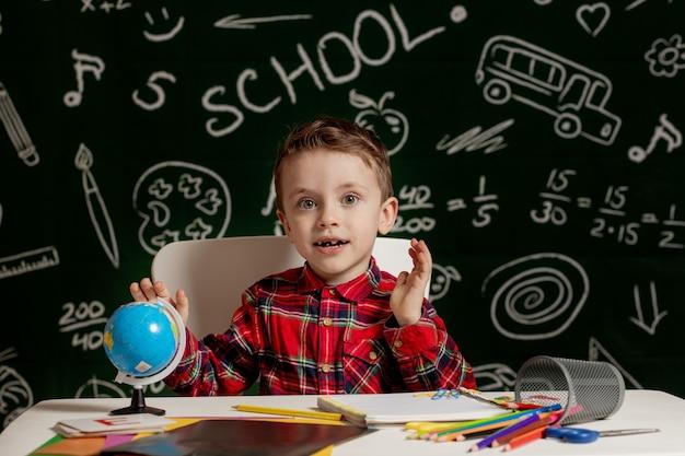 Chłopiec przedszkolak co szkoła praca domowa. chłopiec w szkole z wyrazem twarzy szczęśliwy w pobliżu biurka z przyborów szkolnych. edukacja. nauka przede wszystkim. koncepcja szkoły.