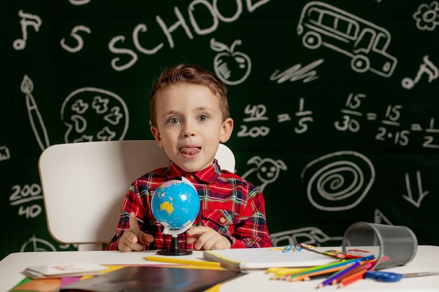 Chłopiec przedszkolak odrabiania lekcji w szkole. uczeń ze szczęśliwym wyrazem twarzy w pobliżu biurka z przyborami szkolnymi