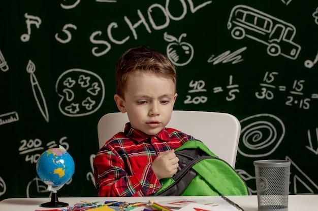 Chłopiec przedszkolak robienia lekcji w szkole.