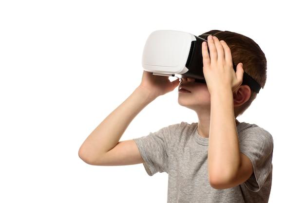 Chłopiec przeżywa wirtualną rzeczywistość. odizolowywa na białym tle.