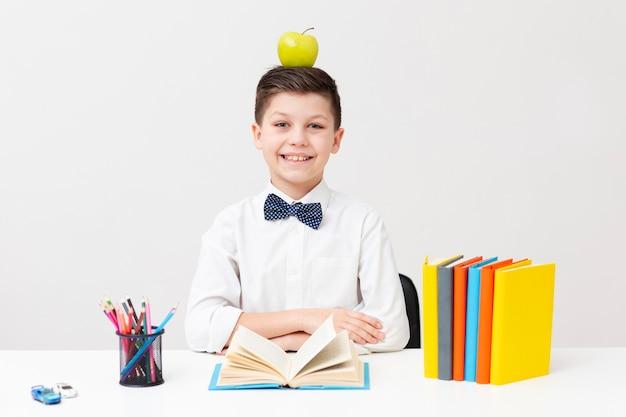 Chłopiec przy biurkiem z jabłkiem na głowie