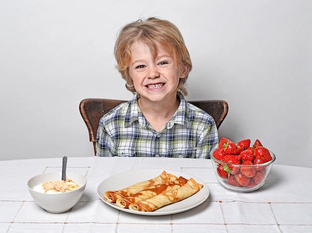 Chłopiec przy śniadaniowym stołem je bliny i truskawki