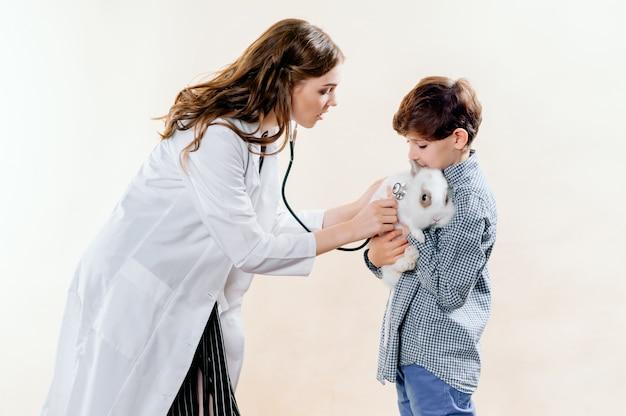 Chłopiec przyniósł królika do weterynarza na badanie, weterynarz przeprowadza badanie