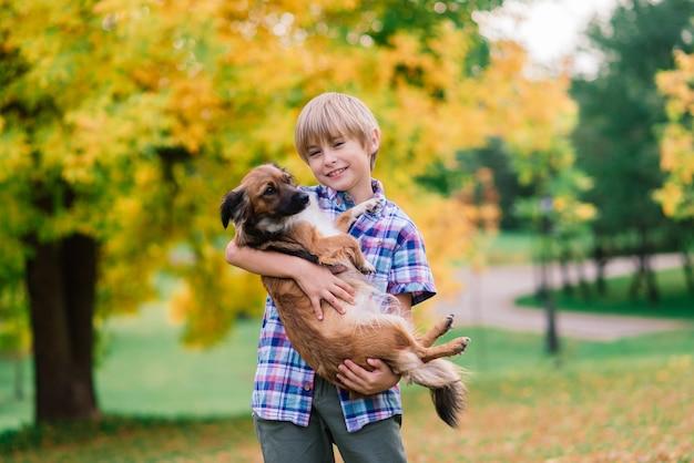 Chłopiec przytula psa i bawi się z jesiennym parkiem miejskim