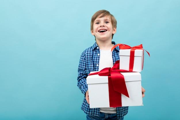 Chłopiec rasy białej posiada wiele białych pudeł z prezentami i raduje się, portret na niebieskim tle