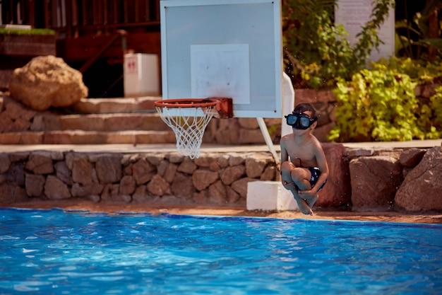 Chłopiec rasy białej zabawy, co fantastyczny skok do basenu w ośrodku. jego ręce i nogi są szeroko otwarte.