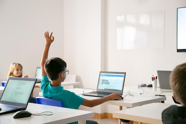 Chłopiec rasy mieszanej w okularach, podnoszący rękę do odpowiedzi podczas lekcji