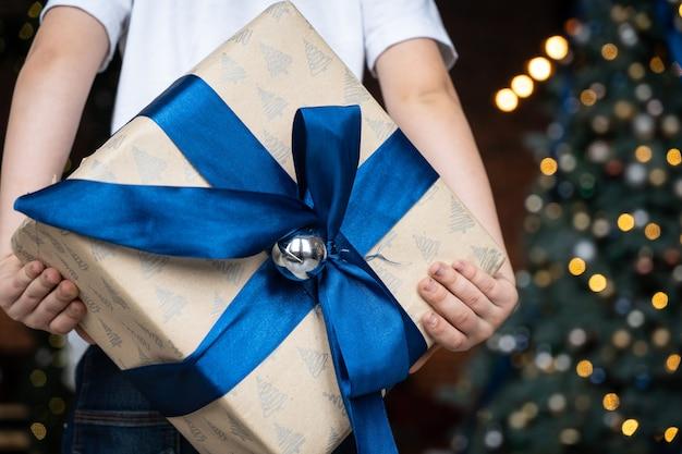 Chłopiec ręce trzymać prezent na boże narodzenie lub nowy rok urządzone pudełko. radość, pokój, miłość