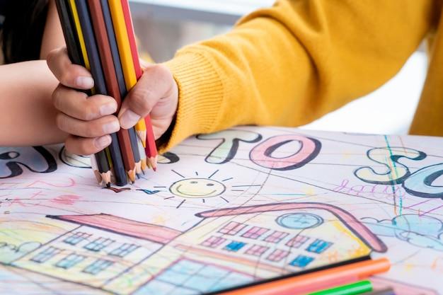 Chłopiec ręka rysuje w dziecinie sztuki sala lekcyjnej