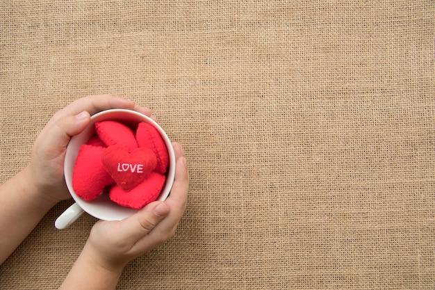 Chłopiec ręki chwyt czerwoni serca w filiżance kawy na workowym tekstury tle