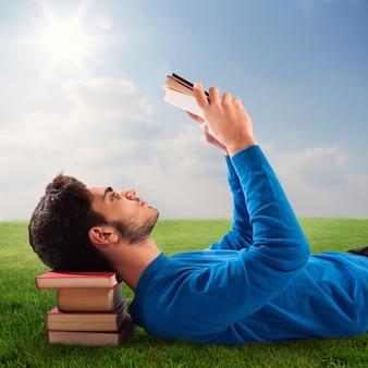 Chłopiec relaksuje się z książką na trawniku