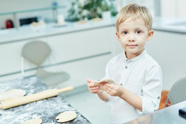 Chłopiec robi ciastu