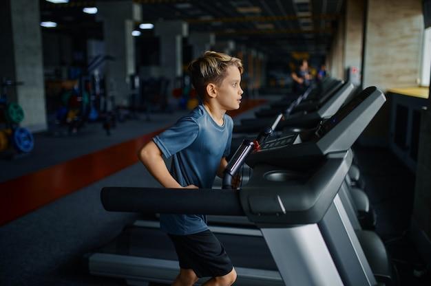 Chłopiec robi ćwiczenia na bieżni w siłowni, uruchomiona maszyna. uczeń na treningu w klubie sportowym, ochronie zdrowia i zdrowym stylu życia