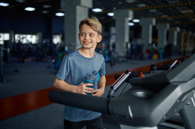 Chłopiec robi ćwiczenia na bieżni w siłowni, uruchomiona maszyna. uczeń o treningu, ochronie zdrowia i zdrowym stylu życia