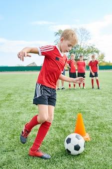 Chłopiec robi ćwiczeniom futbolowym