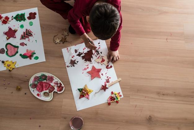Chłopiec robi dekoracje siedząc na podłodze maluje drewniane rękodzieła świąteczne