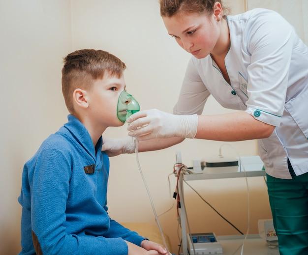 Chłopiec robi inhalaci z nebulizatorem przy kliniką.
