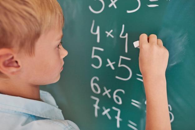 Chłopiec robi kilka ćwiczeń matematycznych